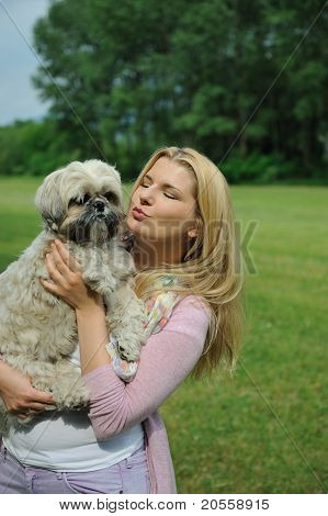 Pretty Casual Woman With Cute Little Shih Tzu Dog Outdoors In A Park