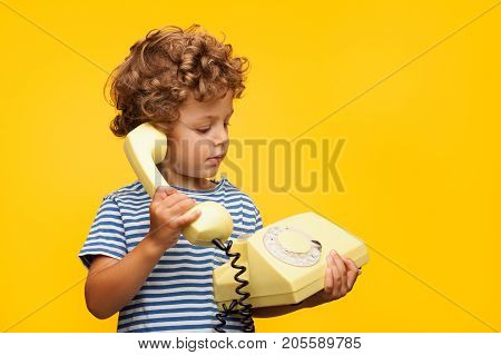 Little curly boy in striped t-shirt holding and talking old phone on orange background.