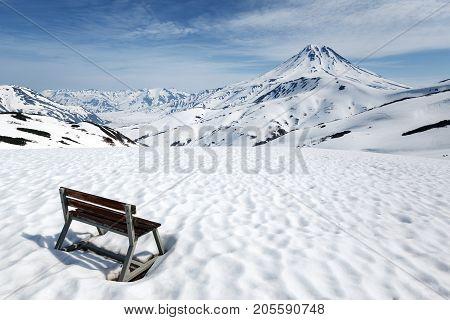 Kamchatka Peninsula volcanic landscape: wooden bench standing in snow on Vilyuchinsky Pass for rest of Kamchatka tourists and travelers observation of Vilyuchinsky Volcano. Russian Far East.