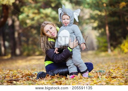 Young woman and daughter dressed in elephant costume poking out their tongues while having fun in autumn park