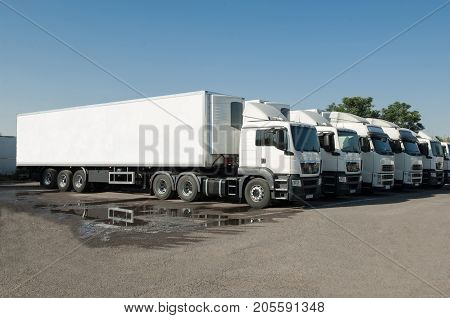 Trucks Stand In The Parking Lot In A Row
