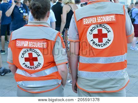 LE MANS, FRANCE - JUNE 16, 2017: Back of two people who work in French Red Crossa first aid team mates in France during parade of 24 hours of Le mans