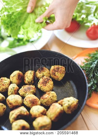 Fried falafel in a cast-iron pan close up. Middle eastern dish falafel pan and dishes with salad on the wooden background. in the background female hands with salad