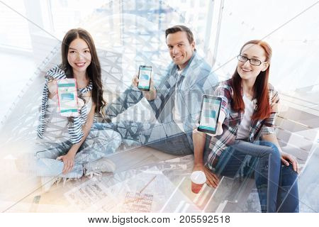 Must have. Group of delighted workers sitting in the office while showing mobile phones to you and expressing happiness