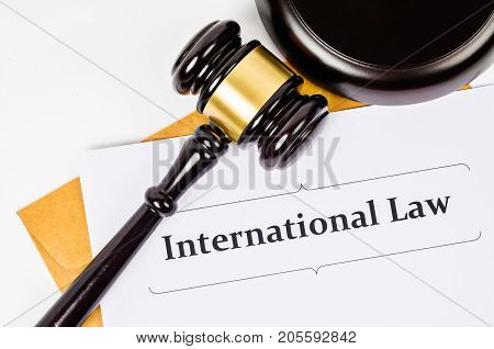 International law documet and wooden judge on white background.