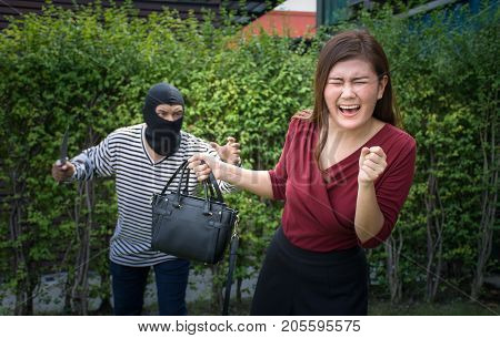 Armed robber and victim with a handbag/Woman ran to escape the bandits ,criminal concept