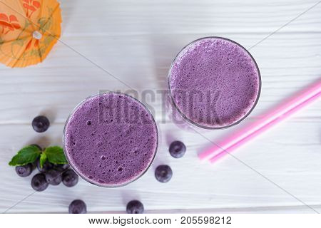 Smoothies, blueberries and blueberries fruit on a white wooden background.