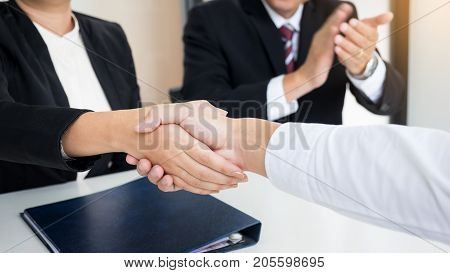 successful business team shaking hands with eachother in the office job interview concept.