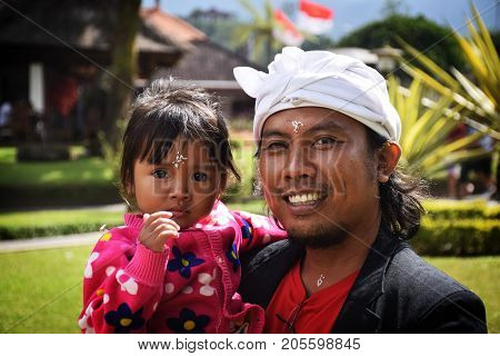 BALI, INDONESIA, AUGUST 22, 2017 - Unidentified balinese man with his little daughter looking and smiling at the camera