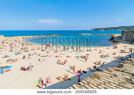 Antibes, France - July 01, 2016: people sunbathing on Plage de la Gravette in Antibes. It is a popular local beach a long stretch of fine white sand at the end of the port.