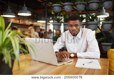 Portrait of african young man in white shirt sitting, working at cafe, with laptop, looking at camera. Businessman listening music, learning, chatting and typing at gadget. Coffe break. freelancer style of job.