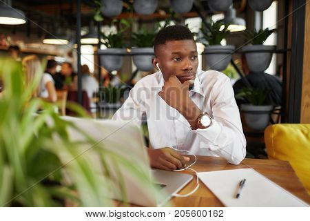 Young african man in white, sitting at table in cafe, thinking, di ided problem, working with laptop, holding chin by hand and looking away. Freelancer male listening musik in headphones. Coffee break.
