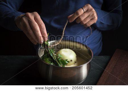 Preparation of bechamel sauce, bouquet of garnishes in hands horizontal