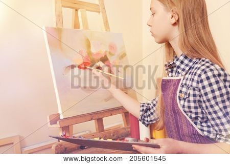 Painting is magical. Totally absorbed in the process of creation girl wearing an apron painting a multi colored abstract picture while taking part in an art class.
