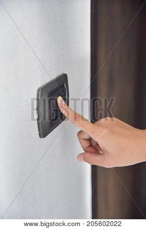 Close up hand turning on or off on dark grey light switch with wall texture background. Copy space.