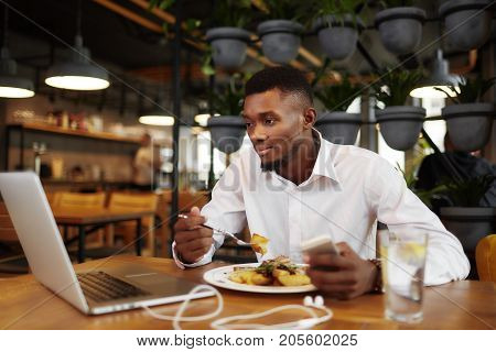 Handsome african man having dinner at stylish cafe, using and looking at laptop. Businessman in white shirt studding at restaurant, watching move, typing at call phone, writing message. Freelancer.