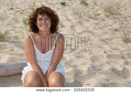 Happy Woman Sitting Outdoor And Thinking Relaxing On A Wooden Bench Under The Tree In A Summer Day