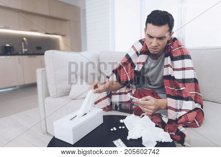 A man with a cold sits on the couch, hiding behind a red rug. Before him lies a bunch of medicines. He pulls on the napkins to blow his nose