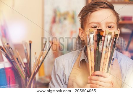 Never getting bored. Radiant youngster smiling and joking while looking into the camera and holding a bunch of painting brushes in studio.