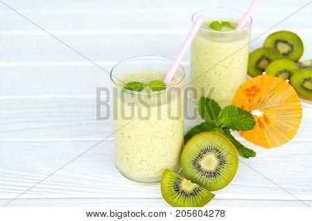Kiwifruit smoothies and kiwi fruit on a white table