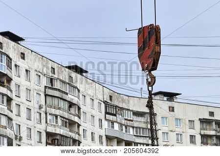 Hook of a construction crane carries materials on construction site near dwelling house in Moscow
