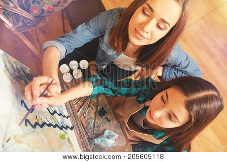 Conveying personal knowledge. Top view of a cheerful young lady and a focused teenage girl holding a painting brush together and sweeping along an art canvas during a painting session.