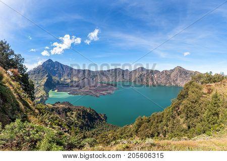 Panorama landscape of active volcano Baru Jari Lake Segara Anak and summit of Rinjani mountain. Lombok island Indonesia.