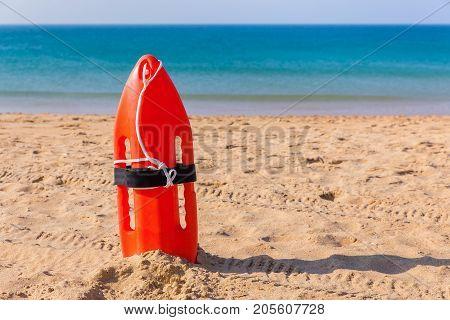 Orange buoy standing on sandy beach with blue sea