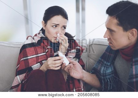 The couple is sitting on the couch wrapped in blankets. Man and woman are sick. A man gives a nasal spray to a woman. She's just flaunting herself
