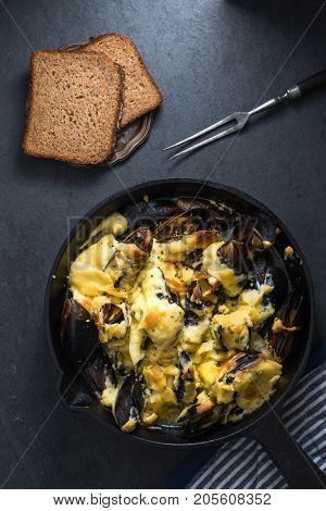 Mussels with cheese sauce in a frying pan, napkin and forks, bread vertical