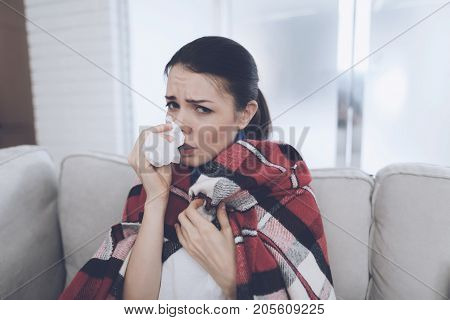 A girl is sitting on a light sofa. She wrapped herself in a red checkered blanket. She is sick with grip and blows her nose