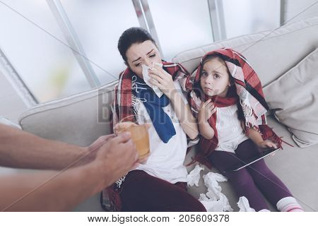 The man brought his wife and daughter hot hot tea. They are looking at something on the girl's tablet. The man brought them therapeutic tea