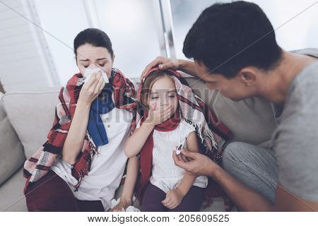 The woman and her daughter are sick and they have a runny nose. They blow their nose, and the man sits next to him and measures the girl's temperature