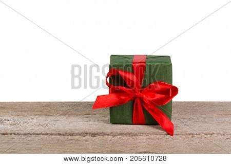 Gift box wrapped with green paper and red satin ribbon on wooden table at white background. Modern presents for any holiday, christmas, valentine or birthday