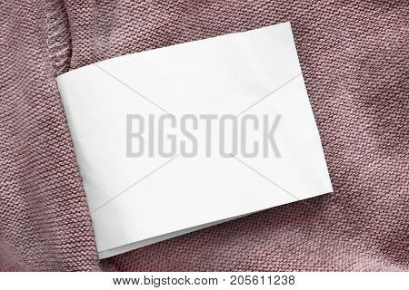 White blank clothes label on pink knitted background closeup