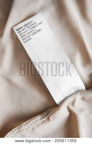 Washing instructions clothes label on beige silk closeup