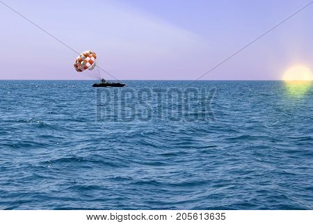 Riding on a parachute behind a boat on the sea boat in the sea on the horizon the boat on the horizon at sunset