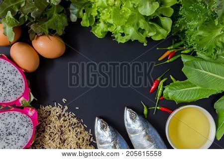 Fresh mackerel fresh vegetables rice oil and fruits on chalkboard background. Concept about eating 5 groups.