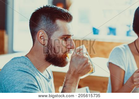 Handsome Young Man With A Beard Drinking Beer From A Glass At The Bar In The Pub And Watching Footba