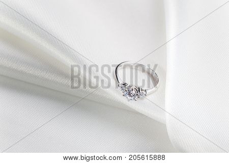beautiful diamond engagement wedding ring on white fabric room for text good for wedding or engagement theme concept
