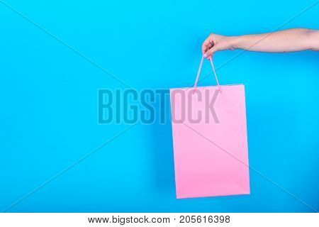 Female Hand Holding Pink Shopping Bags Isolated On Blue (cyan) Background, Free Space, Close Up. Sal