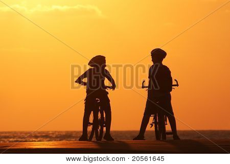 Silhouette of two kids on bicycles standing on the pear on Mediterranean Sea at sunset.