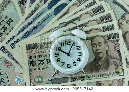 white alarm clock on pile of japanese yen banknotes as time count down or deadline concept.