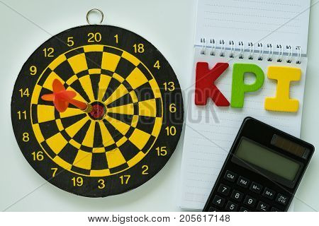 colorful wooden alphabet KPI and calculator on white paper note and dartboard.