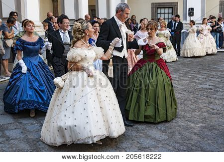 NAPLES ITALY - MAY 12: Ladies and gentlemen in ball suits of the 19th century inside the Chiostro of St. Lorenzo on May 12 2013 in Naples Italy.