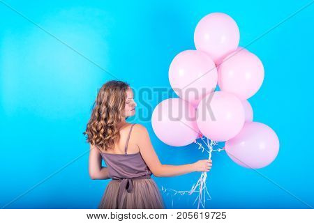 Beautiful Young Woman Having Fun With Pink Helium Air Balloons On Blue Background. Girl With Curly H