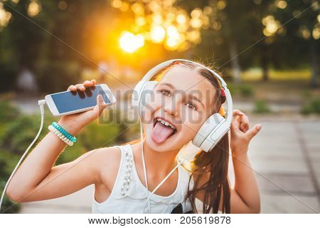 funny girl with headphones showing tongue and smiling, cool teenager with white headphones at sunset, childhood and hi-tech concept