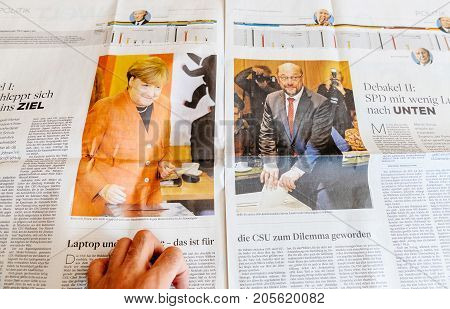 PARIS FRANCE - SEP 25 2017: International newspaper with portrait of Angela Merkel and Martin Schulz after voting - election in Germany for the Chancellor of Germany the head of the federal government