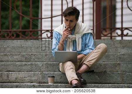 Modern communication. Male with bad habits. Remote work, student coffee break, freelancer outdoors, technology concept