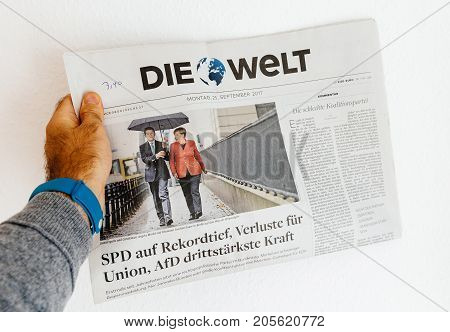 PARIS FRANCE - SEP 25 2017: International newspaper with portrait of Angela Merkel and husband Joachim Sauer after winning the election in Germany for the Chancellor of Germany